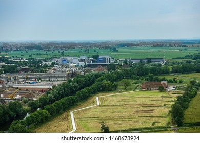 Diksmuide, Flanders, Belgium -  June 19, 2019: View on farms and farm land and industrial area with Deceuninck plant from up IJzertoren, tallest peace monument of WW 1. Greens, grays and reds.