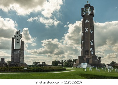 Diksmuide, Flanders, Belgium - September 15, 2018: Tallest peace monument in Flanders, called IJzertoren. brown bricks, white figures, blue sky with clouds, green lawn and PAX crypt.