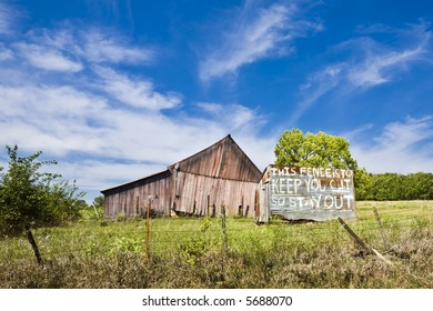 Dilapidated barn sits behind a fence and warning sign on a farm near Lawrence, Kansas