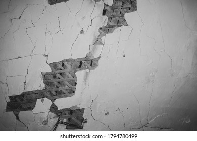 Dilapidated ceiling of an old house. damaged wall with a hole with timber frame. abstract background of ruined surface