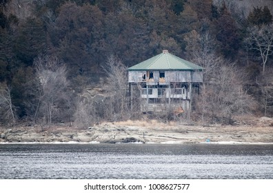 A dilapidated house on stilts stands tall over the river that once flooded it