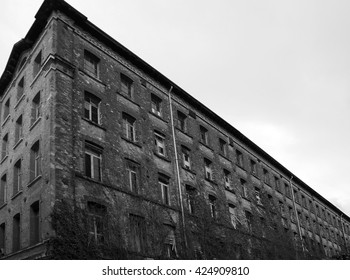 dilapidated industrial building with facing bricks and broken windows