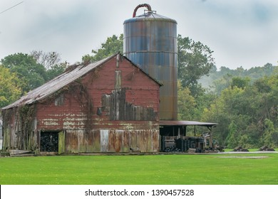 Dilapidated Red Barn in a Green Pasture next to an old Rusty Barn Silo surrounded by a wooded forest in Southern Indiana America's Heartland.