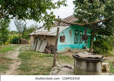 Dilapidated village house/Old vintage countryside house in a state of decay with a water well in the yard.