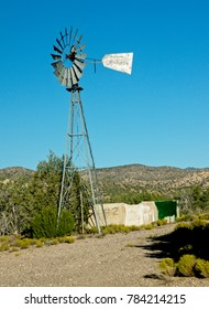 Dilapidated western water wheel, iconic symbol of the Old West, with pure blue sky.