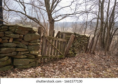 A dilapidated wooden fence allowing access through a stone wall. The wall looks like it is from a colonial period williamsburg home in the countryside.