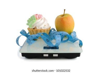 The dilemma of cake or an apple wrapped in the centimeter scale on white background (isolated)