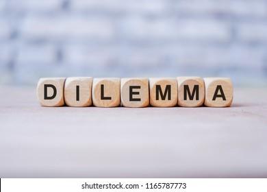 Dilemma word written on wood block