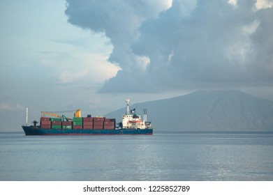 Dili Timor Leste on November 26, 2010: ship was full with containers with background of mountain and cloudy sky