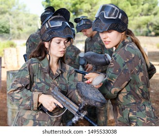 Diligent  cheerful  woman paintball coach in full gear instructing female player about marker gun before match