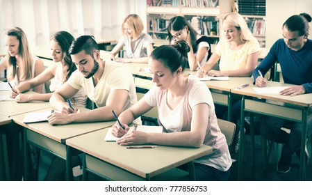 Diligent college students sitting at their desks in a classroom