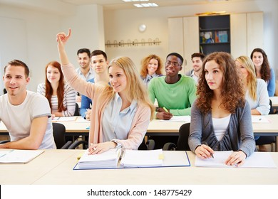 Diligent female student lifting hand in university seminar classroom