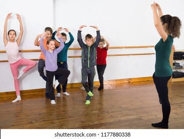 Diligent friendly  ballet dancers exercising in ballroom