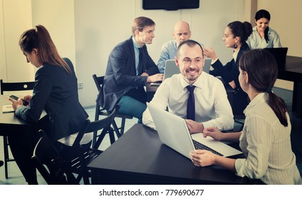 Diligent friendly glad coworkers working effectively on business project together