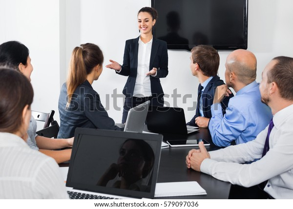 Diligent friendly smiling manager making speech during business meeting in office