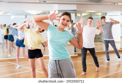 Diligent friendly smiling teenagers learn dance movements in dance class