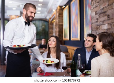 Diligent friendly smiling   waiter with dishes serving man and woman friendly company indoors