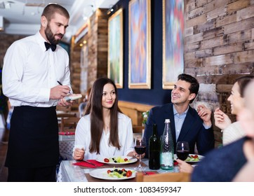 Diligent friendly smiling   waiter with notebook taking order from friendly company indoors