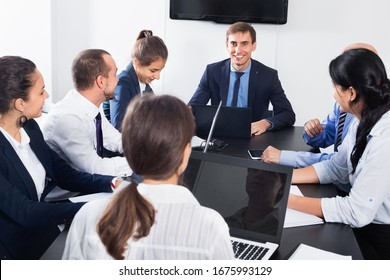 Diligent friendly team member explaining issue on project to coworkers in office