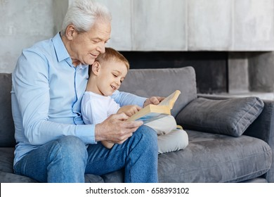 Diligent handsome granddad reading for his grandson
