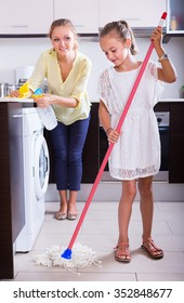 Diligent little girl helping joyful mother to clean in the kitchen at home