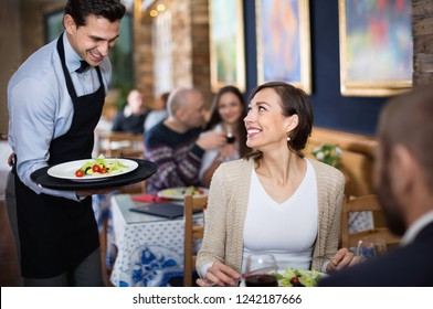 Diligent  pleasant waiter with dishes serving man and woman friendly company indoors