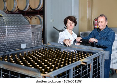 Diligent positive glad expert and wine maker inspect containers with bottles of red wine