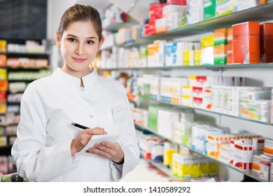 Diligent positive smiling female specialist is attentively stocktaking medicines with notebook near shelves in pharmacy.