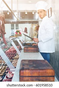 Diligent professional cook sniffing freshly cooked dish at store