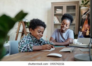 Un écolier consciencieux faisant des notes devant le moniteur avec son professeur à l'écran pendant la leçon en ligne