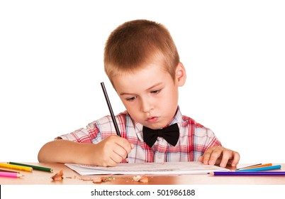 Diligent schoolboy sitting at the table, paints in an album for drawing isolated on a white background.