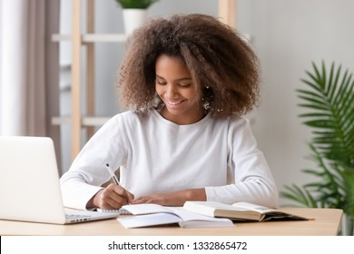 Diligent schoolgirl sitting at home or classroom, desk filled with books training materials, teen study with laptop writing using textbook preparing for test at school. Education and knowledge concept