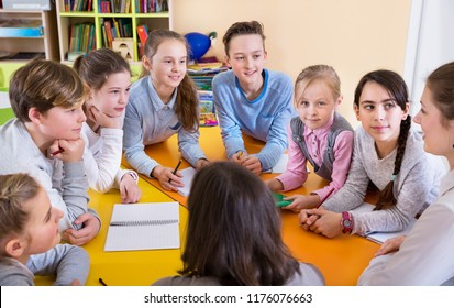 Diligent schoolkids sitting at the classroom attentively listening teacher