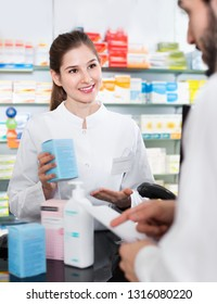 Diligent  smiling female specialist is helping male client choose prescription medicine in pharmacy.