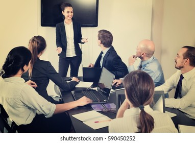Diligent smiling manager making speech during business meeting in office