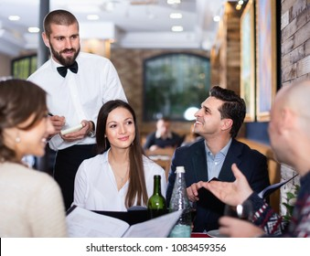 Diligent  smiling waiter with notebook taking order from friendly company indoors