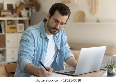 Diligent student. Concentrated millennial man studying online sit by laptop computer at home office making notes of distant lecture. Remote trainee take exam via e-learning web platform prepare task