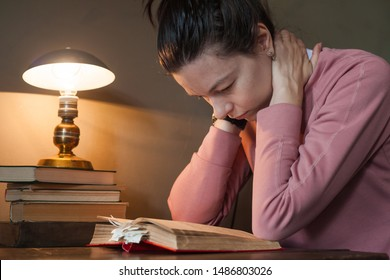Diligent student. A tired girl student leaned over a thick book with many bookmarks, at a tiny table, under a warm lamp. The girl carefully reads, doubts, turns. Side view.