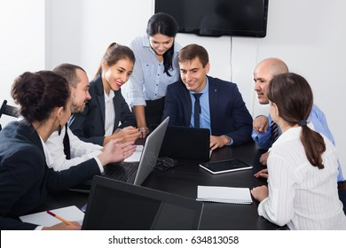 Diligent team member explaining issue on project to coworkers in office