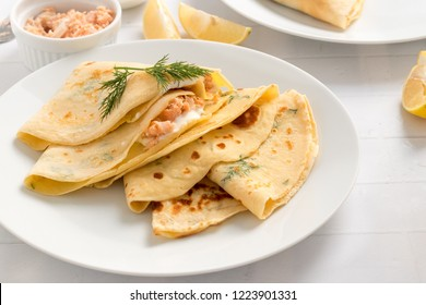 Dill crepes filled with cream cheese and smoked salmon on white plate.