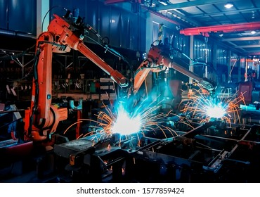 The dim large factory robotic arm is being welded and assembled