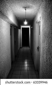 Dim light glowing in dark underground corridor.