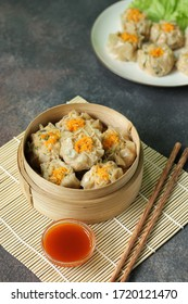 Dim Sum in bamboo steamer with sauce and chopstick.  Dim sum on plate blurred background. Asian Food