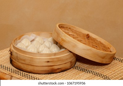 dim sum steam cooked in a bamboo pot - side view on a bamboo mat and a wooden table