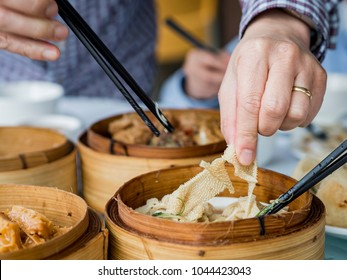 Dim sum style ginger and scallion tripe. This delicious treat served in a bamboo steamer is very popular in most overseas Chinese restaurants. Finger and chopsticks tearing a piece apart.