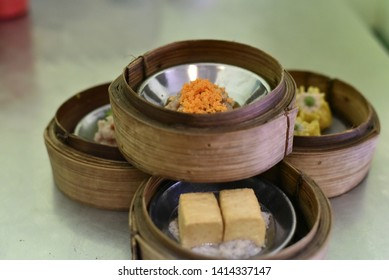 Dim sum or Tim sum (Dumplings) in stainless steel dish and bamboo steamer box at a Chinese restaurant,Tim sum as breakfast in southern part of Thailand,Chinese food concept.
