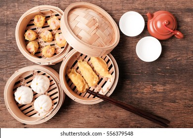 Dim Sum(Chinese cuisine) in bamboo steamed and teapot on wooden table top.
