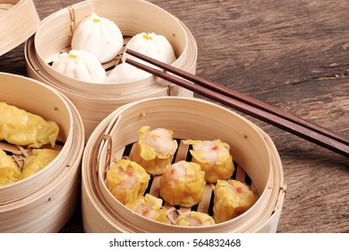 Dim Sum(Chinese cuisine) : Steamed bun, dumpling and shumai in bamboo steamed on wooden table top.