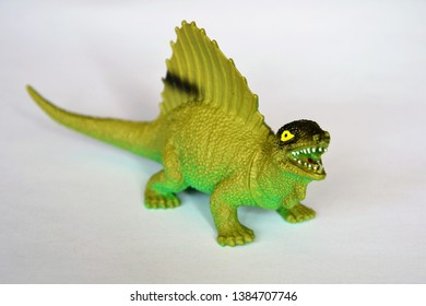 Dimetrodon with the large neural spine sail on its back. An extinct genus of synapsids that lived during the Early Permian. Dinosaur green plastic toy on the white background.