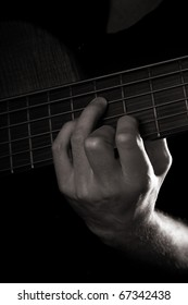 Diminished seventh chord (A-dim7), playing six-string electric bass guitar; fretting left hand; toned monochrome image;